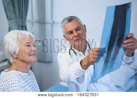 Doctor discussing x-ray report with senior patient in hospital