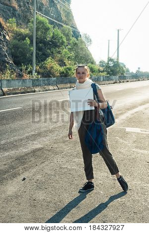 Young Woman Hitchhiker Standing On The Road