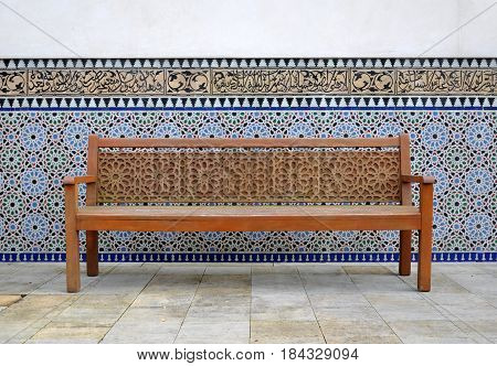 Berlin, Germany - April 13, 2017: Wooden park bench with beautiful patterns in the East garden. Gardens of the world in Berlin.