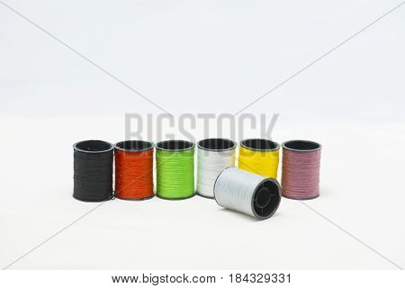 Isolated spool of colorful thread and needle on white background.