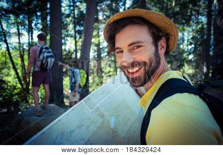 Portrait of smiling man holding map in forest on a sunny day
