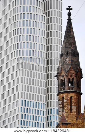 Berlin, Germany - April 14, 2017: Tower of Kaiser Wilhelm Memorial Church in Kurfurstendamm on a background of white modern skyscraper.