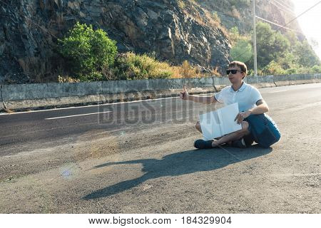 Young Man Hitchhiker Sitting On The Road