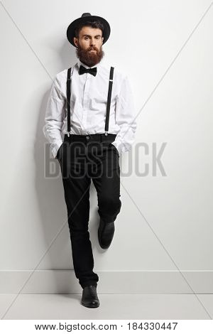 Full length portrait of an elegant man with suspenders and a bow tie leaning against a white wall