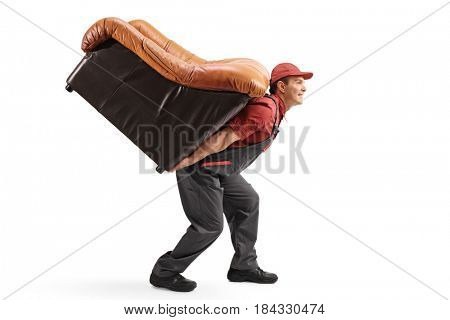 Profile shot of a mover carrying an armchair on his back isolated on white background