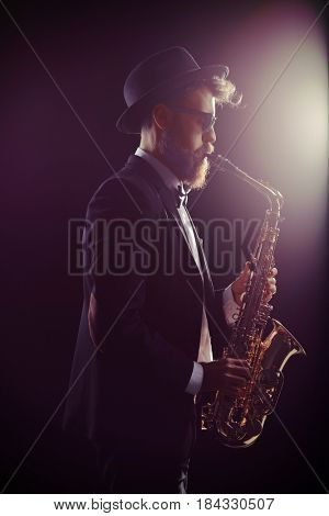 Profile shot of a bearded man performing on a saxophone