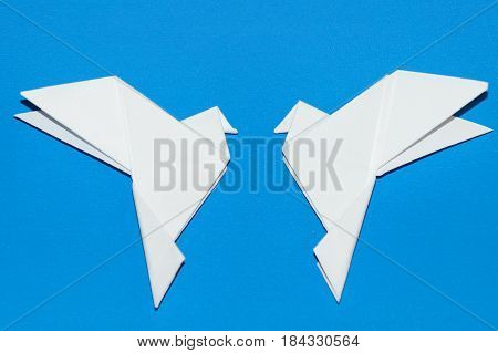 Origami pigeons on a blue background. A white dove in flight is isolated on a blue background. A paper dove is isolated on a blue background.