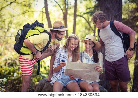 Group of friends looking at map in forest