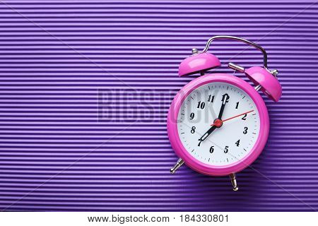 Pink alarm clock on the purple background