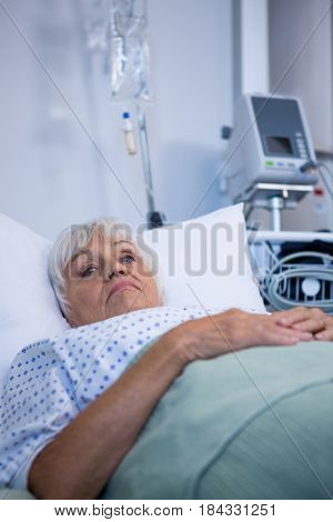 Worried senior patient lying on bed in hospital