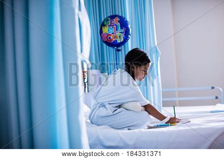 Girl drawing picture in a book while sitting on hospital bed