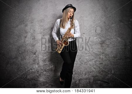 Attractive young woman playing a saxophone and leaning against a rusty gray wall