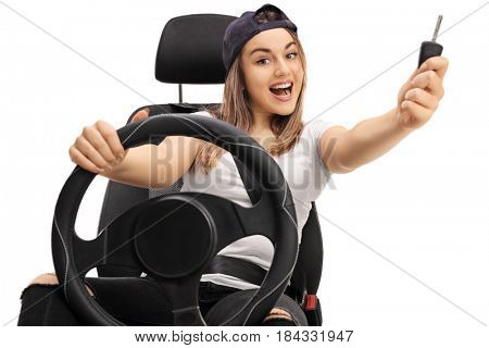 Joyful teenage girl with a car key sitting in a car seat isolated on white background