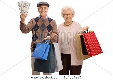 Cheerful seniors with bundles of money and shopping bags isolated on white background