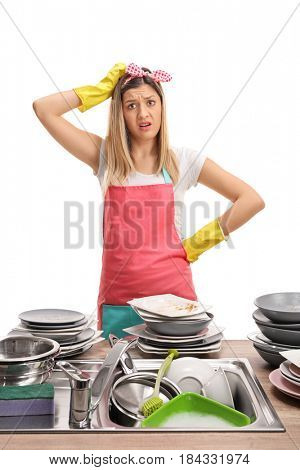 Upset young woman behind a sink filled with dirty plates isolated on white background