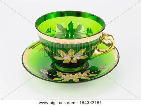 Antique transparent green glass teacup and saucer isolated on white backgroound