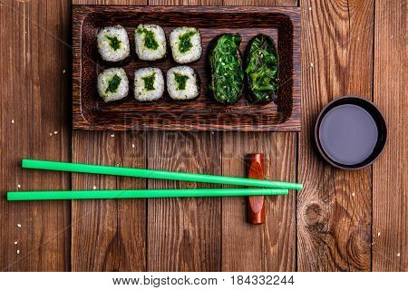 Japanese rolls, green sticks, sauce on a wooden table