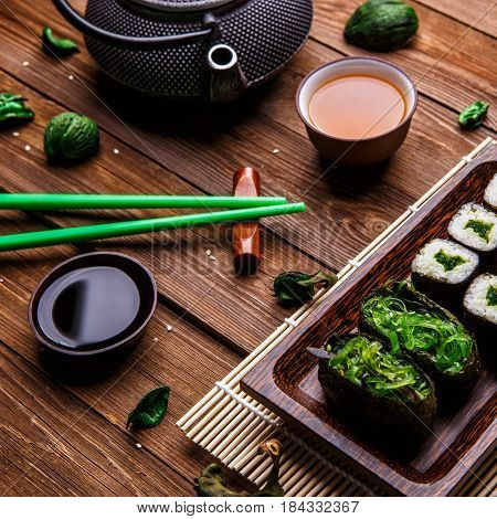 Photo of table with sesame, rolls, sauce and chopsticks