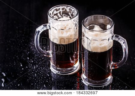 Photo of two mugs of beer on empty black background