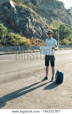 Young Man Hitchhiker Standing On The Road