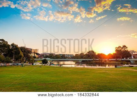 Adelaide Australia - April 5 2017: Torrens river foot bridge with buildings at the background at sunset viewed from King William street towards west.