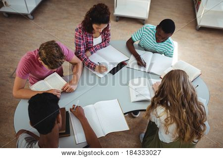 High angle view of attentive classmates studying in library at school