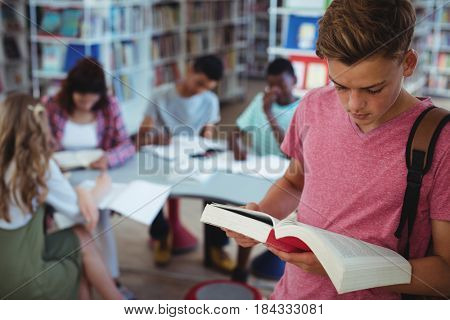 Schoolboy reading book with his classmates studying in background at school