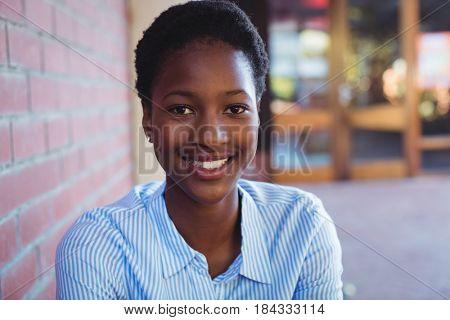 Portrait of happy schoolgirl sitting beside brick wall in school campus
