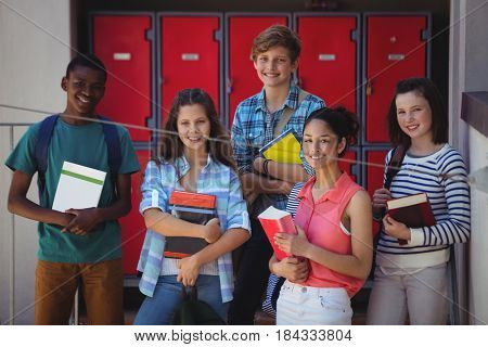 Portrait of students holding books standing in school campus