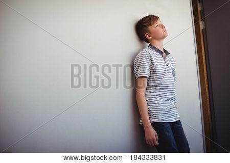 Sad schoolboy leaning head against wall in corridor of school
