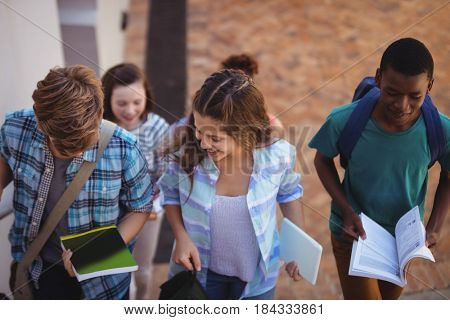 Group of students holding books and digital tablet walking through school campus