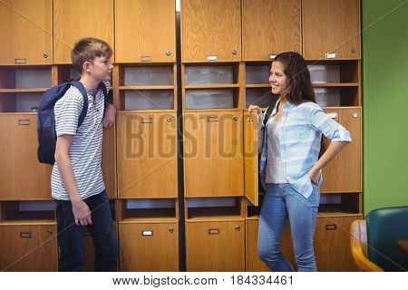 Happy students interacting with each other in locker room at school