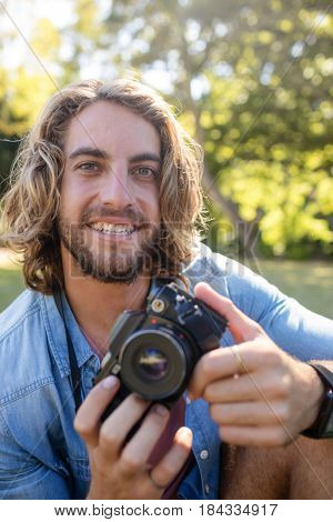 Portrait of smiling man sitting in park with digital camera