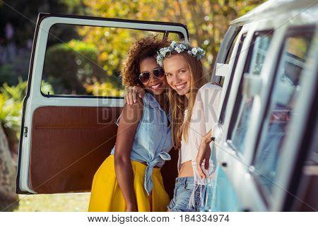 Portrait of two female friends standing near campervan in park