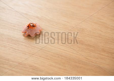 Orange color pencil shaving in a flower shape on a white background