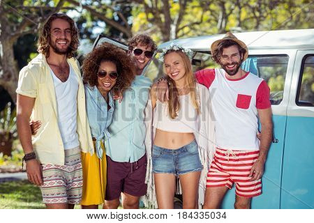 Portrait of happy friends standing together with arms around in park