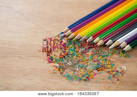 Colored pencils arranged in diagonal line with pencil shavings on wooden background