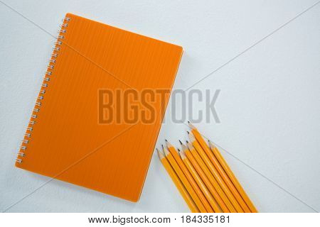 Close-up of yellow color pencils with book on white background