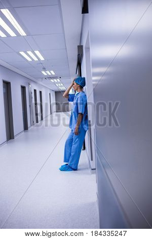 Sad surgeon leaning on wall in corridor at hospital