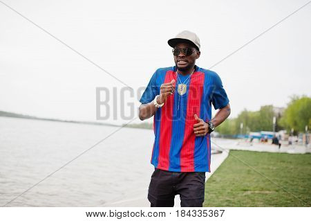 Stylish African American Boy Running Against Lake Wear At Cap, Football T-shirt And Sunglasses. Blac