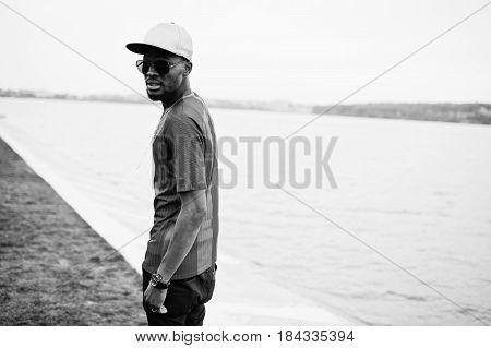 Stylish African American Boy Wear At Cap, Football T-shirt And Sunglasses. Black Sports Man Portrait