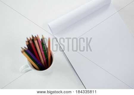 Colored pencils kept in mug with notepad on white background