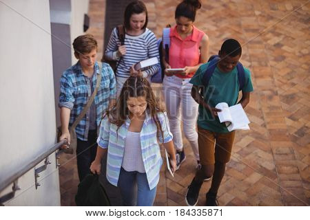 Group of students holding books and digital tablet walking in school campus