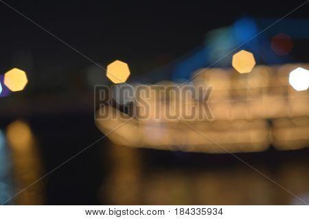 Photography lens blurr effect of dhow cruise. Abstract night city lights background.