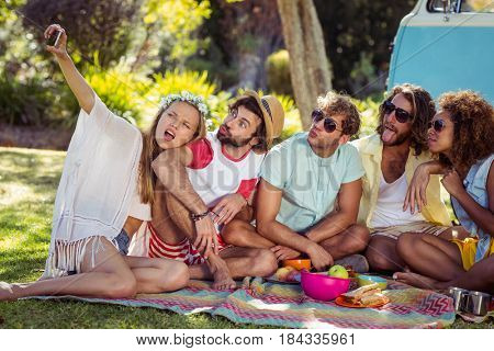 Group of happy friend taking a selfie in park on a sunny day