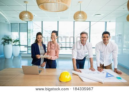 Portrait of smiling architects standing together in office