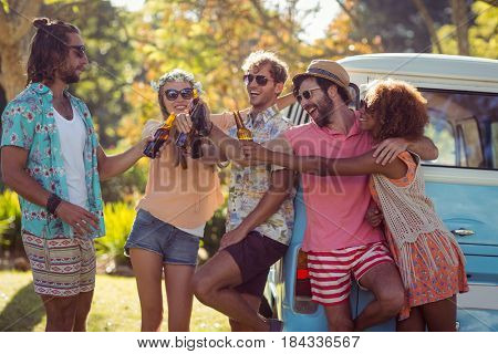 Group of friends toasting beer bottles in park