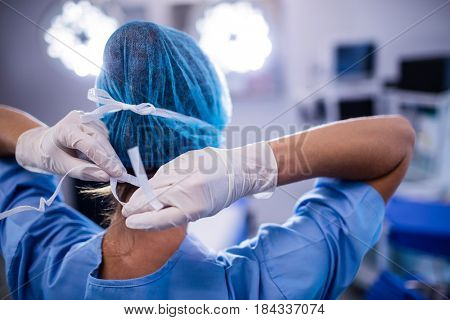 Female nurse tying surgical mask in operation theater at hospital