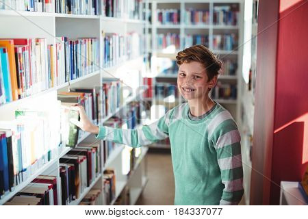 Portrait of schoolboy selecting book in library at school