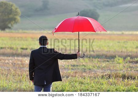 Businessman with a red umbrella in a field - insurance and protection concept